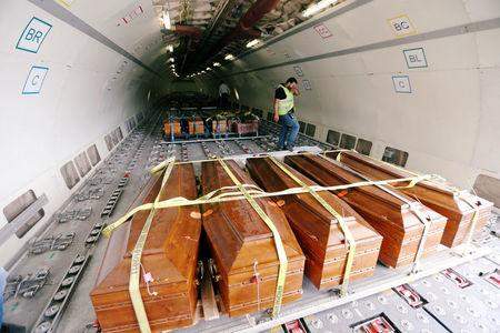 Coffins containing the remains of the bodies of Egyptian Copts killed by Islamic State militants in Sirte are carried by the plane to be transferred to Egypt, in Misrata, Libya May 14, 2018. REUTERS/Ismail Zitouny