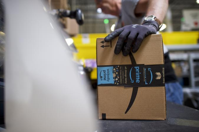 ROBBINSVILLE, NJ - AUGUST 1:  A worker boxes orders at the Amazon Fulfillment Center on August 1, 2017 in Robbinsville, New Jersey.  The more than 1 million square feet facility holds tens of millions of products, features more than 14 miles of conveyor belts, and employs more than 4,000 workers who pick, pack, and ship orders.  Tomorrow Amazon will host a jobs fair to hire 50,000 positions in their fulfillment centers nationwide.  (Photo by Mark Makela/Getty Images)