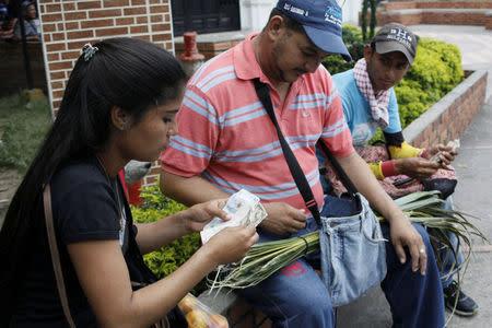 Genesis Materan (L) counts Colombian pesos as she sells vegetables and fruits bought in Venezuela to a customer in Cucuta, Colombia December 15, 2017. REUTERS/Carlos Eduardo Ramirez