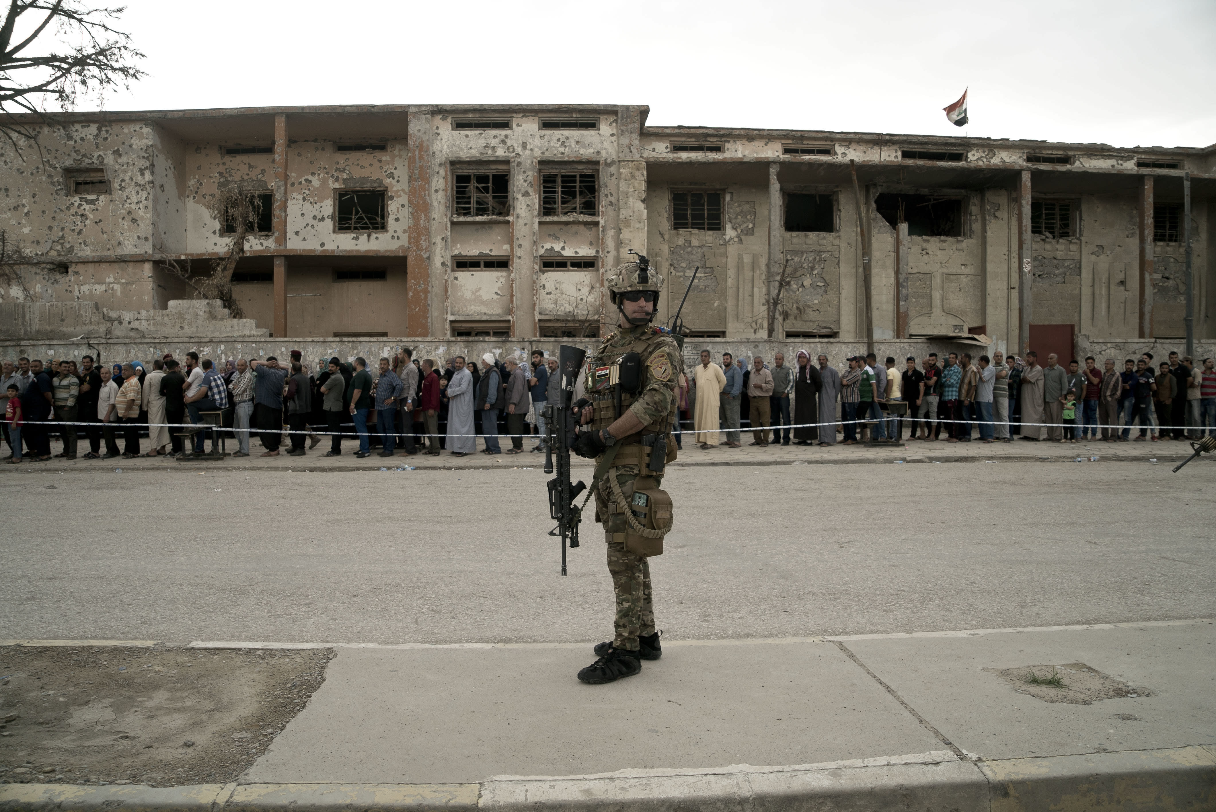 <p>Iraqis wait in a long line to cast their votes in the country's parliamentary elections at a polling site in a damaged building in west Mosul, Iraq, Saturday, May 12, 2018. This is the first parliamentary election since the militant group was ousted from the city. (Photo: Maya Alleruzzo/AP) </p>