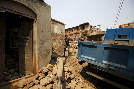 A man works to rebuild a house a year after the 2015 earthquakes in Bhaktapur