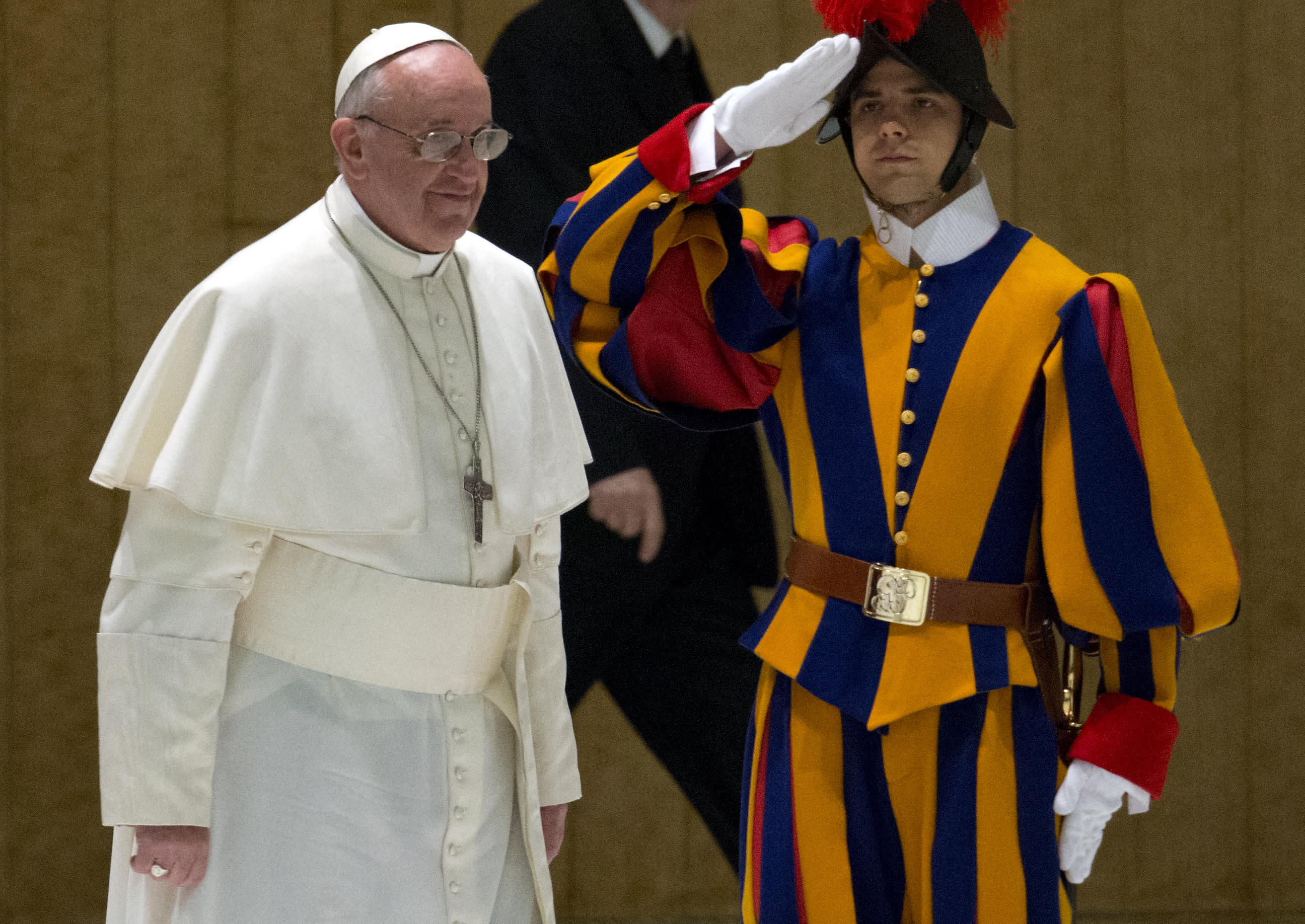 Pope Francis walks past a Swiss guard as he arrives for a meeting with the media at the Pope VI hall, at the Vatican, Saturday, March 16, 2013. (AP Photo/Michael Sohn)
