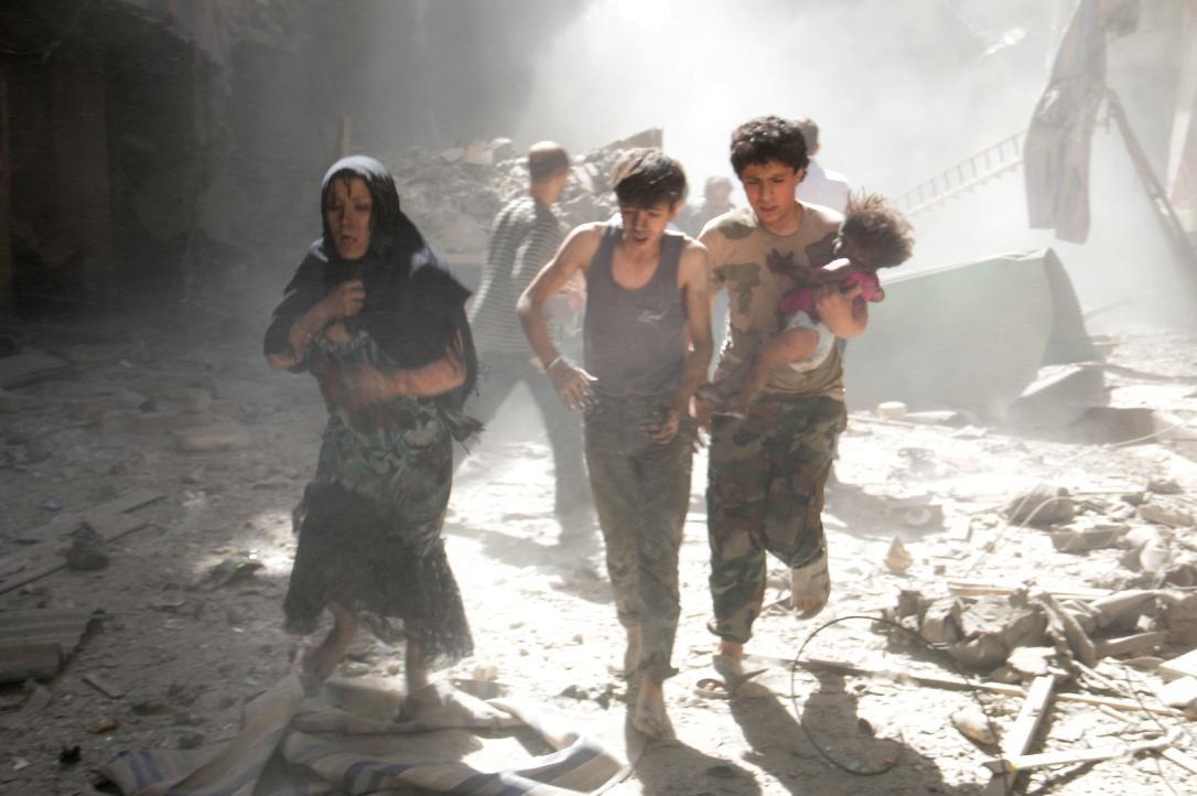 A Syrian woman and youths flee the site of a reported barrel-bomb attack by government forces in the northern city of Aleppo on June 26, 2014