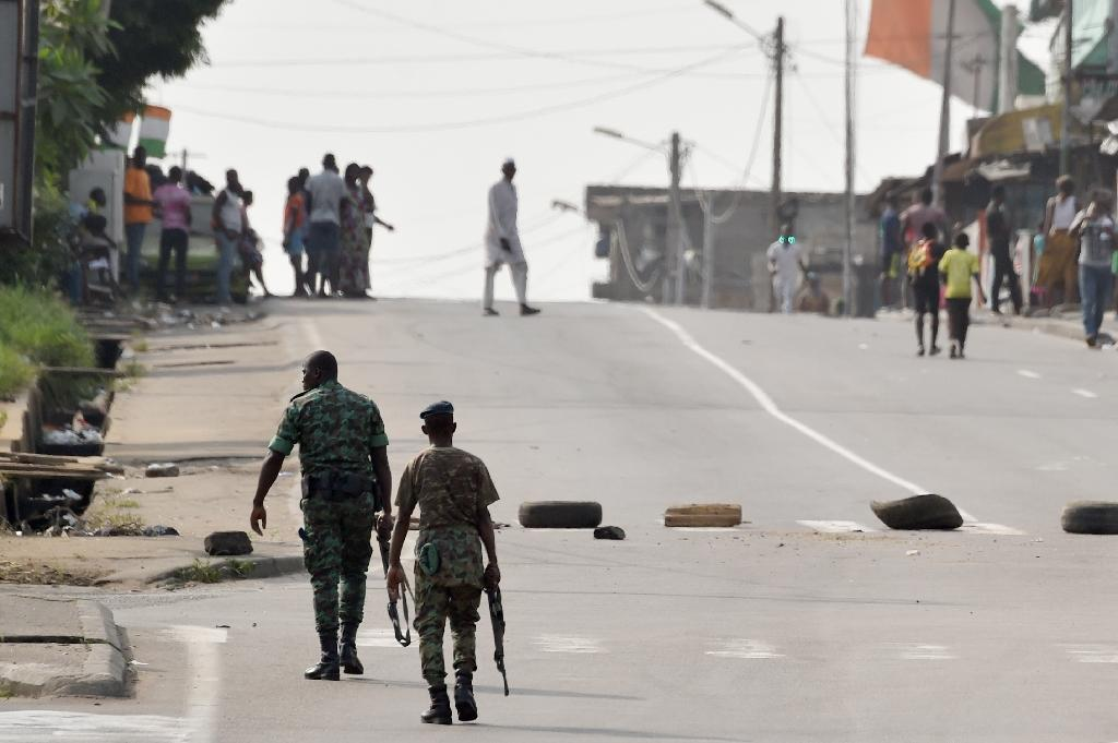 Soldiers patrol near tyres blocking the road in the Plateau business district of the Ivorian capital Abidjan on January 7, 2017 as angry troops took to the streets demanding salary hikes