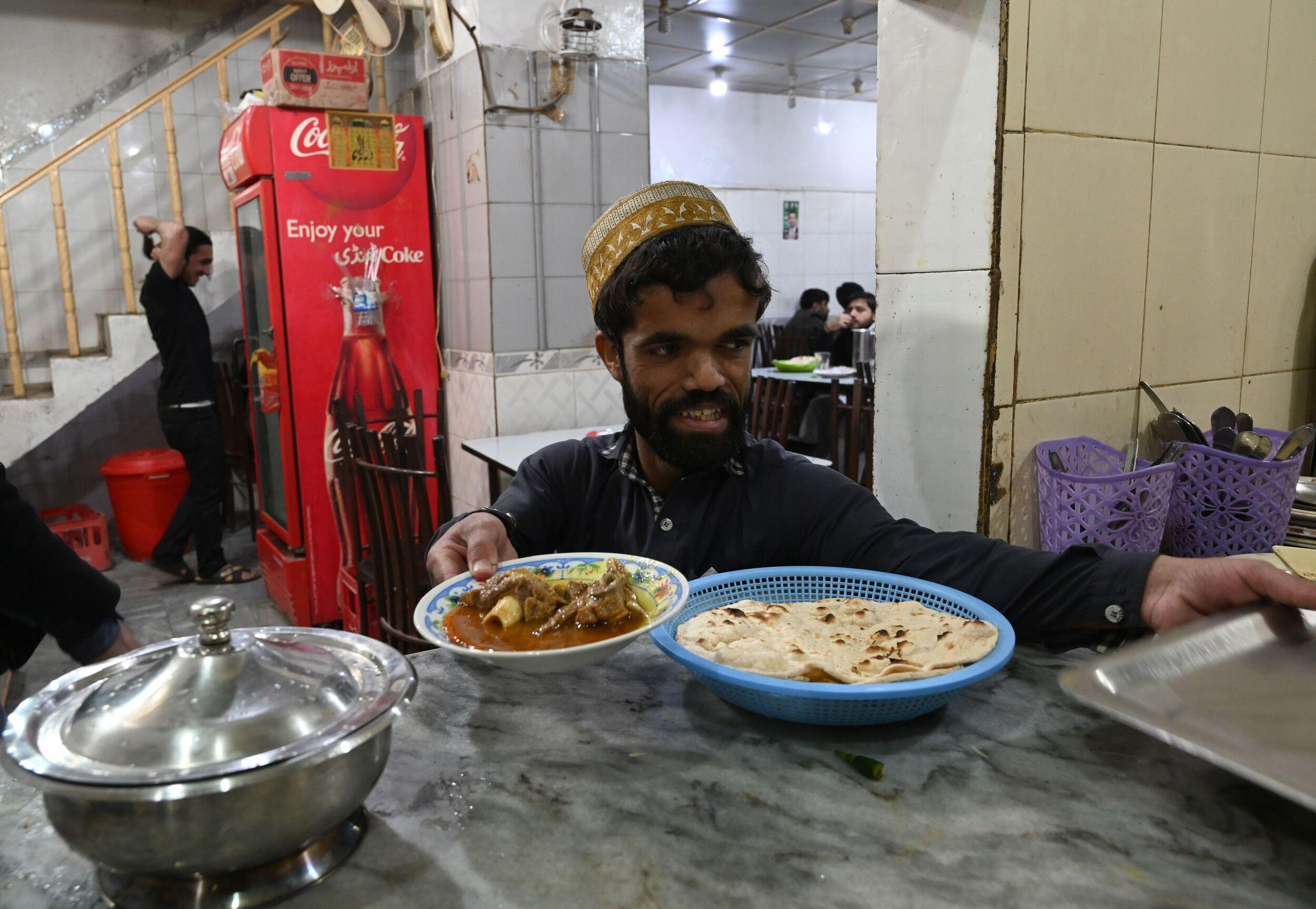 In this picture taken on February 22, 2019, Pakistani waiter Rozi Khan, 25, who resembles US actor Peter Dinklage, prepares to serve food to customers at Dilbar Hotel in Rawalpindi. - Rozi Khan had never heard of the Game of Thrones -- or its hugely popular character Tyrion Lannister -- until his striking resemblance to the dwarf anti-hero got heads turning at home. (Photo by AAMIR QURESHI / AFP) / To go with PAKISTAN-LIFESTYLE-TELEVISION-ENTERTAINMENT        (Photo credit should read AAMIR QURESHI/AFP/Getty Images)