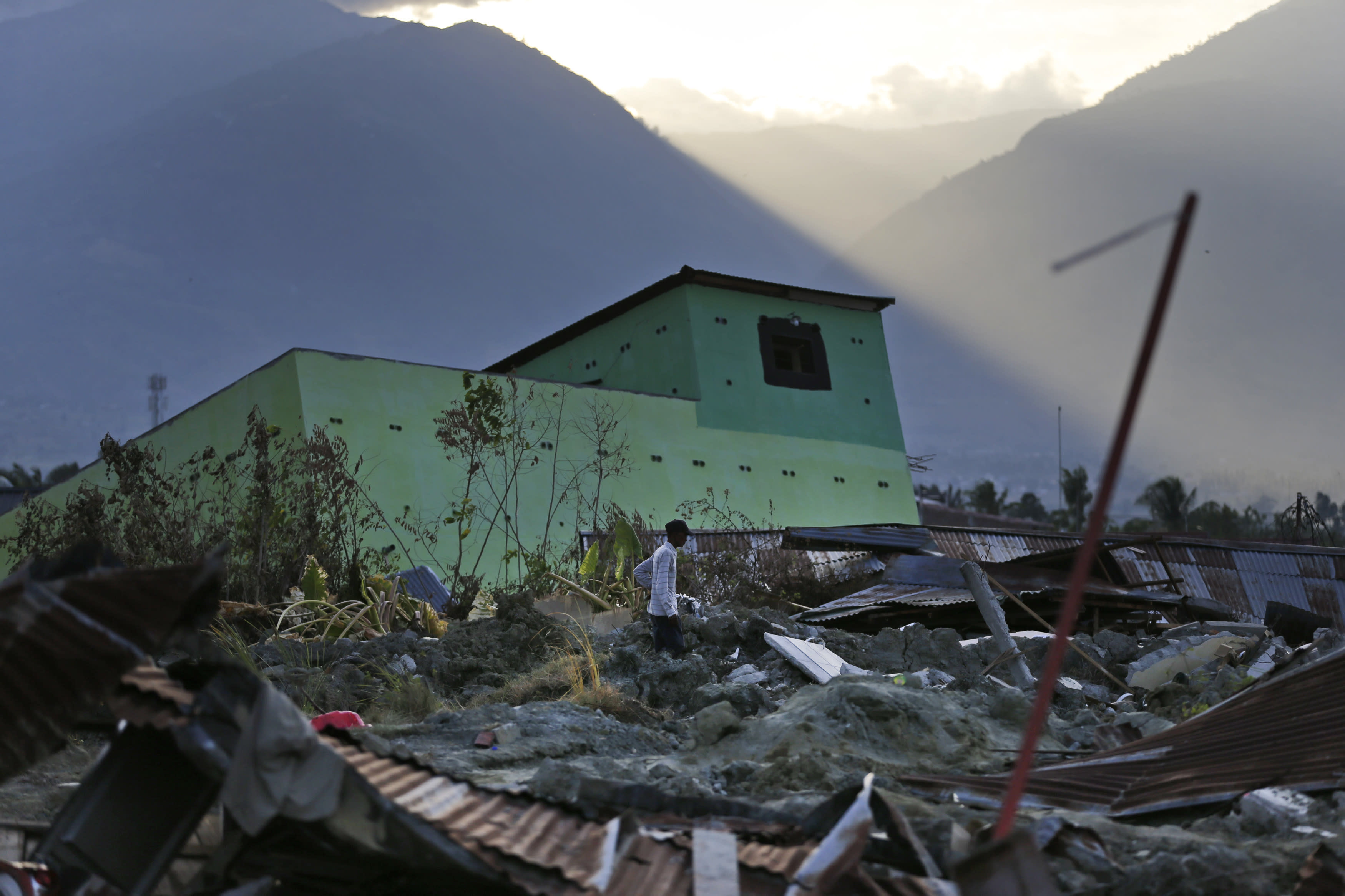 A man surveys the damage suffered byPetobo neighborhood which was wiped out by earthquake-triggered liquefaction as the sun set in Palu, Central Sulawesi, Indonesia, Sunday, Oct. 7, 2018. Indonesia's disaster agency said the number of dead had climbed and many more people could be buried, especially in the Palu neighborhoods of Petobo and Balaroa, where thousands of homes were damaged or sucked into deep mud when the Sept. 28 quake caused loose soil to liquefy. (AP Photo/Dita Alangkara)