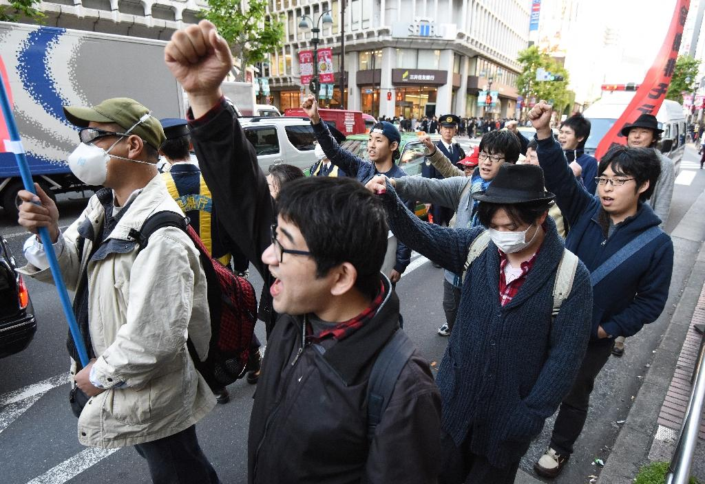 """Members of a group of men calling themselves """"Losers with Women"""" march through the Shibuya shopping district in Tokyo shouting anti-Christmas slogans on December 19, 2015"""