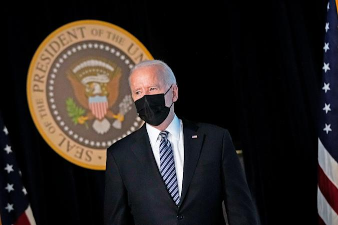 Joseph Biden stands in front of the presidential seal.