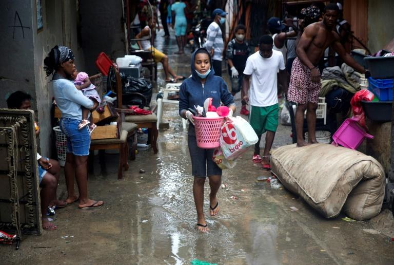 People remove wet belongings from their homes as rain falls from Tropical Storm Laura in Santo Domingo, Dominican Republic
