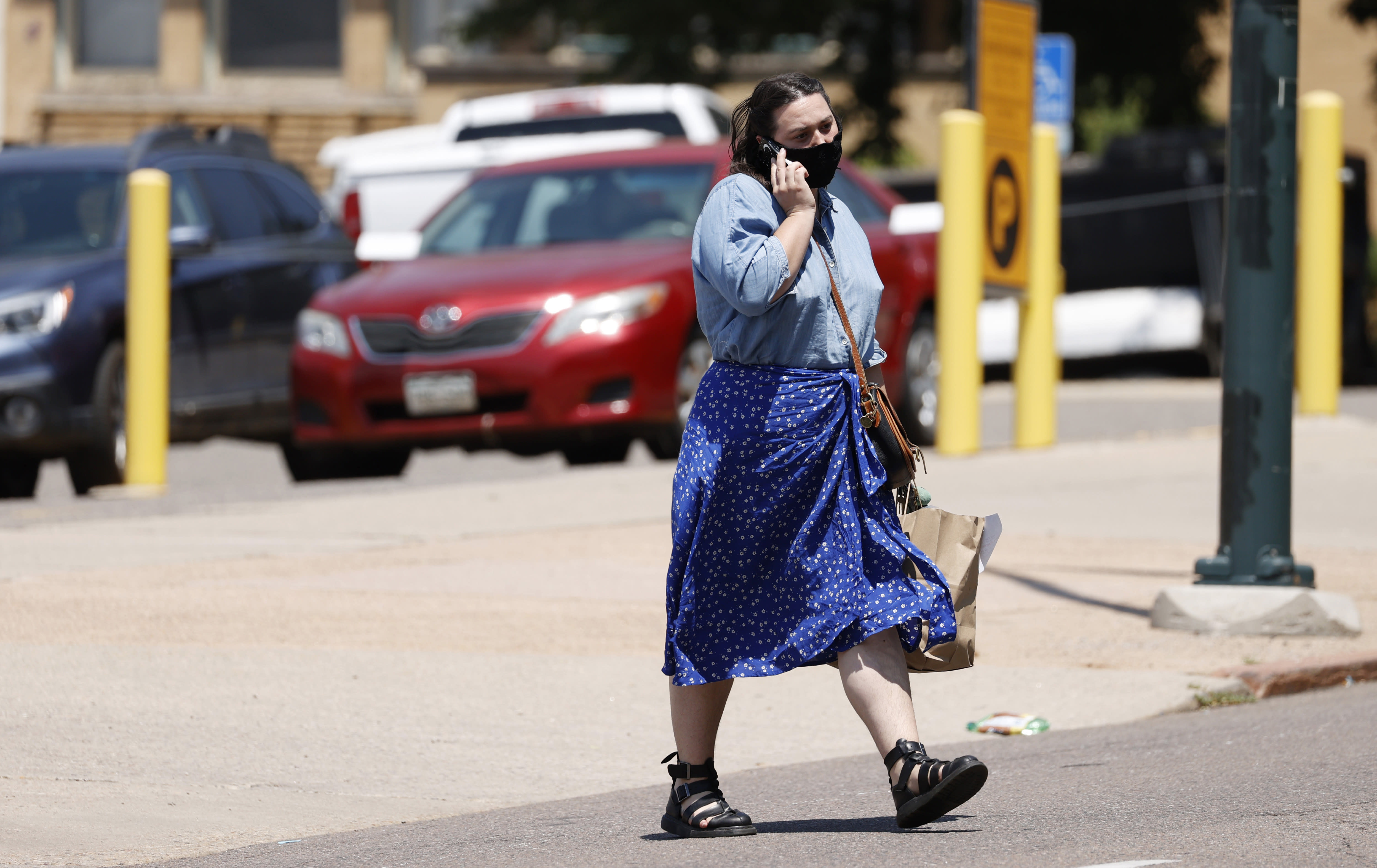 A pedestrian wears a face mask while chatting on a mobile device while crossing Grant Street near 8th Avenue Tuesday, July 21, 2020, in Denver. (AP Photo/David Zalubowski)