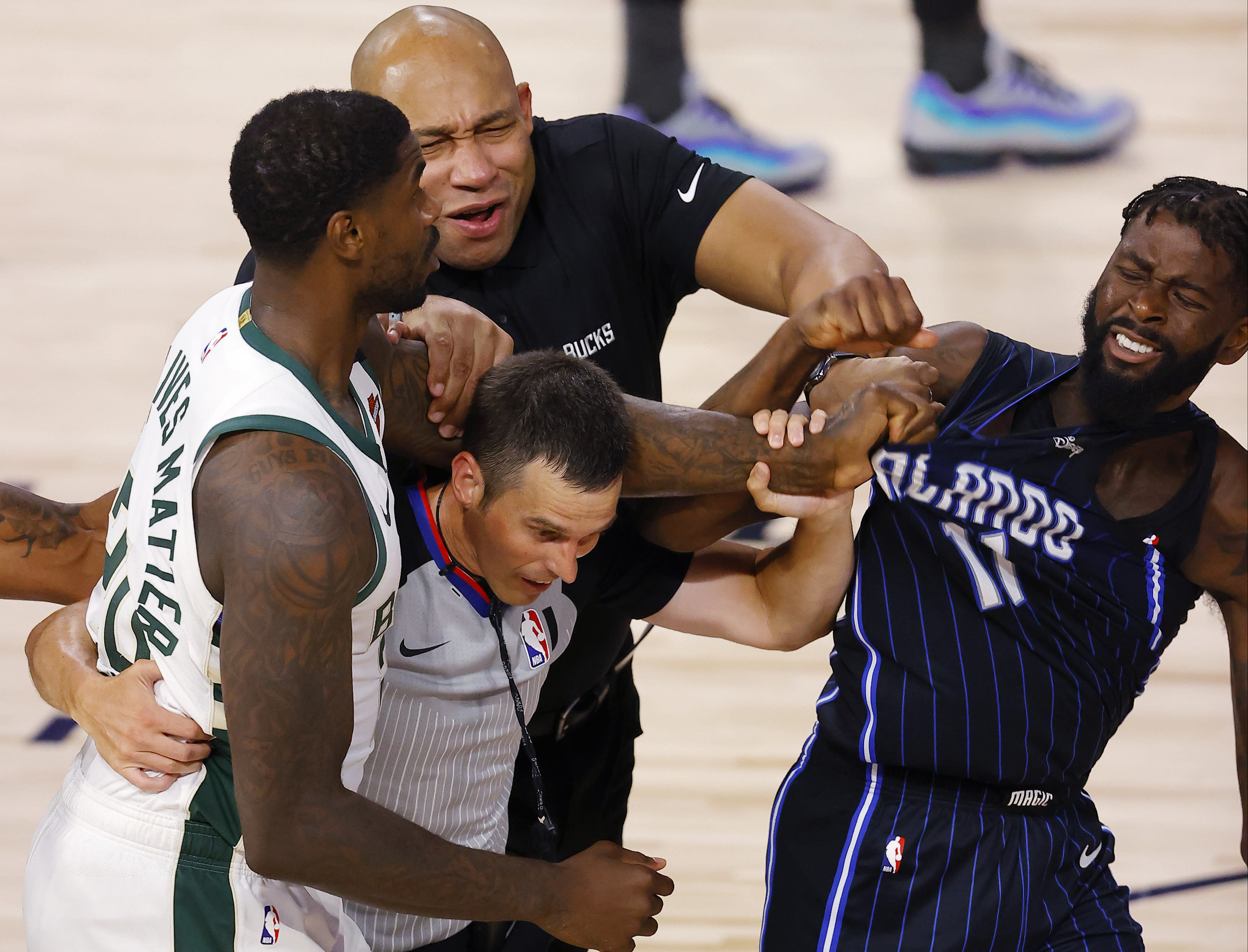 Milwaukee Bucks' Marvin Williams (20) grabs the jersey of Orlando Magic's James Ennis III (11) as referee Kevin Scott and Bucks assistant coach Darvin Ham tries to break it up during Game 3 of an NBA basketball first-round playoff series, Saturday, Aug. 22, 2020, in Lake Buena Vista, Fla. (Mike Ehrmann/Pool Photo via AP)