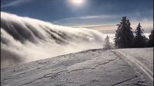 Impressive Wave of Fog Rolls Over Mountain Range in Switzerland