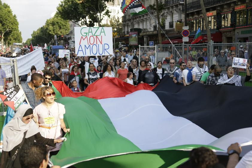 """Protestors hold a Palestinian flag and a placard reading """"Gaza My Love"""", as they take part in a demonstration on July 23, 2014 in Paris (AFP Photo/Kenzo Tribouillard)"""