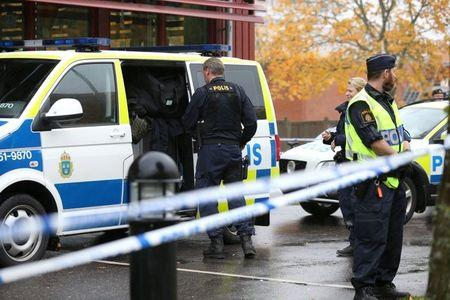 FILE PHOTO: Police officers stand guard at a cordoned area after a masked man attacked people with a sword at a school in Trollhattan, western Sweden October 22, 2015. REUTERS/Bjorn Larsson Rosvall/TT News Agency/File Photo