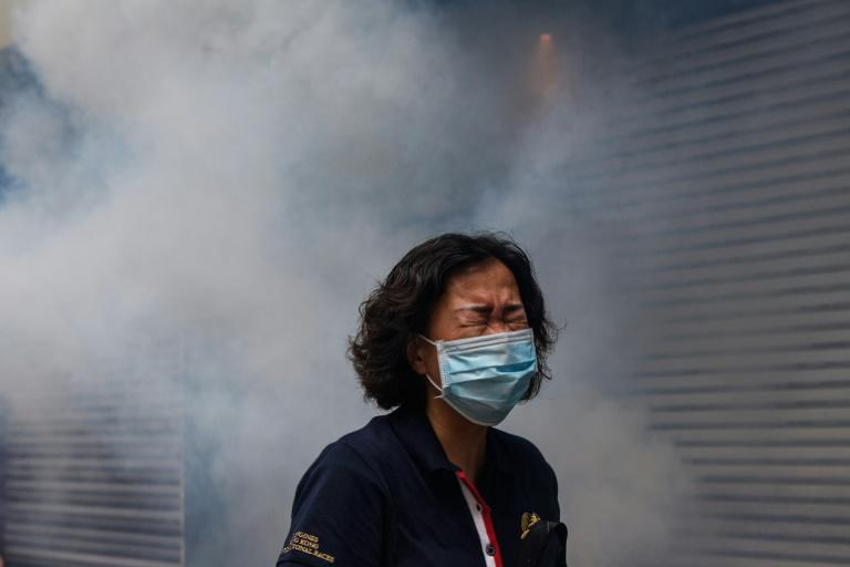 A woman reacts after riot police fired tear gas to disperse protesters taking part in a pro-democracy rally against a proposed new security law in Hong Kong (AFP Photo/ANTHONY WALLACE)
