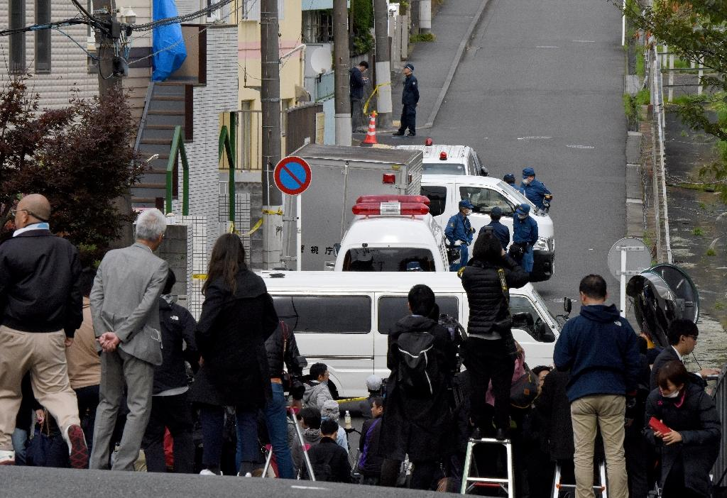 Journalists gather in front of an apartment (partially covered with a blue sheet) where the headless bodies were found (AFP Photo/Toru YAMANAKA)