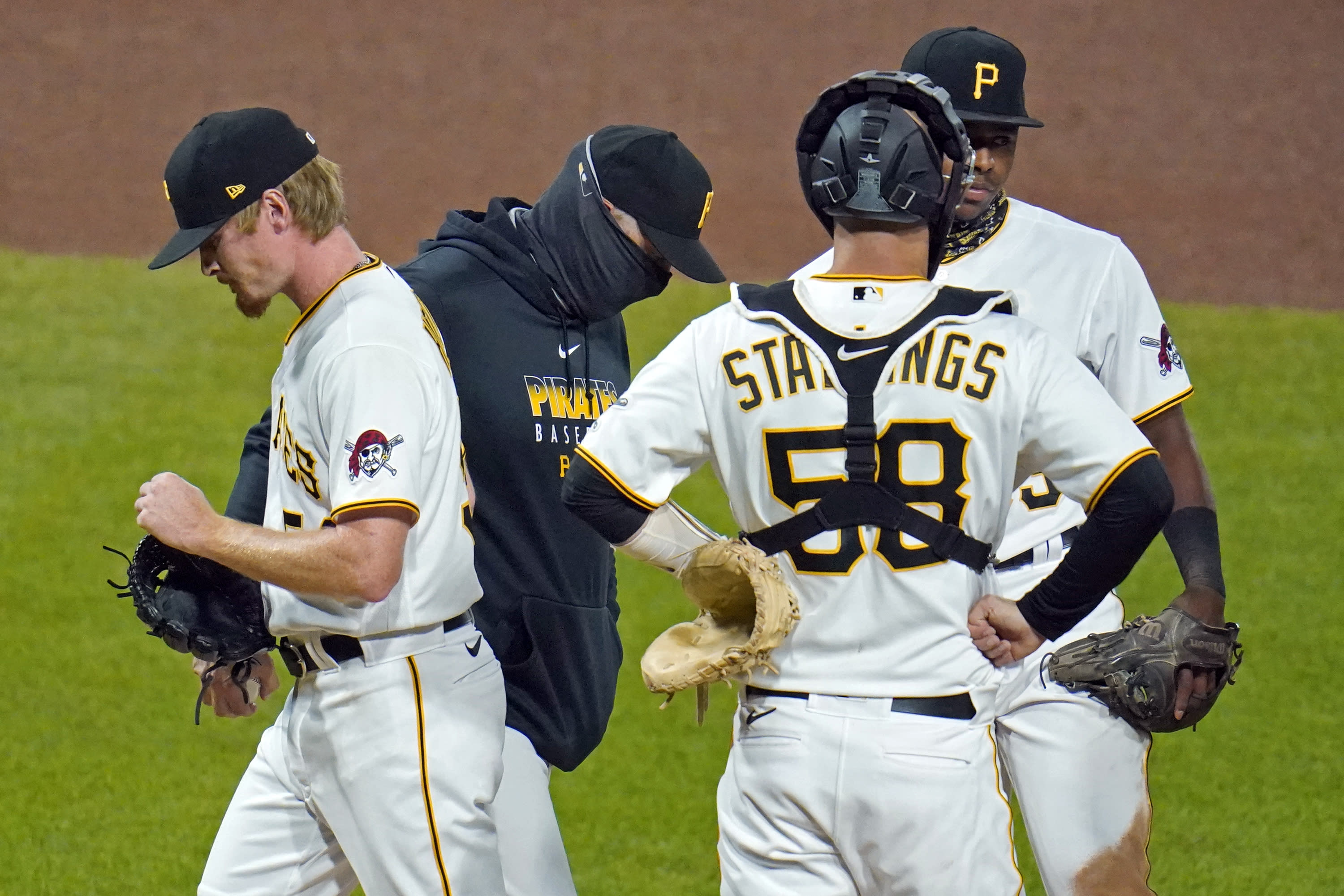 Pittsburgh Pirates relief pitcher Sam Howard, left, walks off the mound after handing the ball to manager Derek Shelton, second from left, during the seventh inning of the team's baseball game against the St. Louis Cardinals in Pittsburgh, Saturday, Sept. 19, 2020. (AP Photo/Gene J. Puskar)