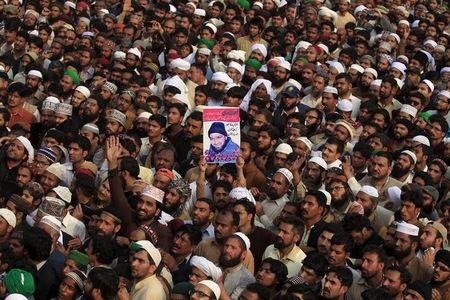 A man holds up the picture of Mumtaz Qadri while attending his funeral prayer at the Liaqat Bagh in Rawalpindi,