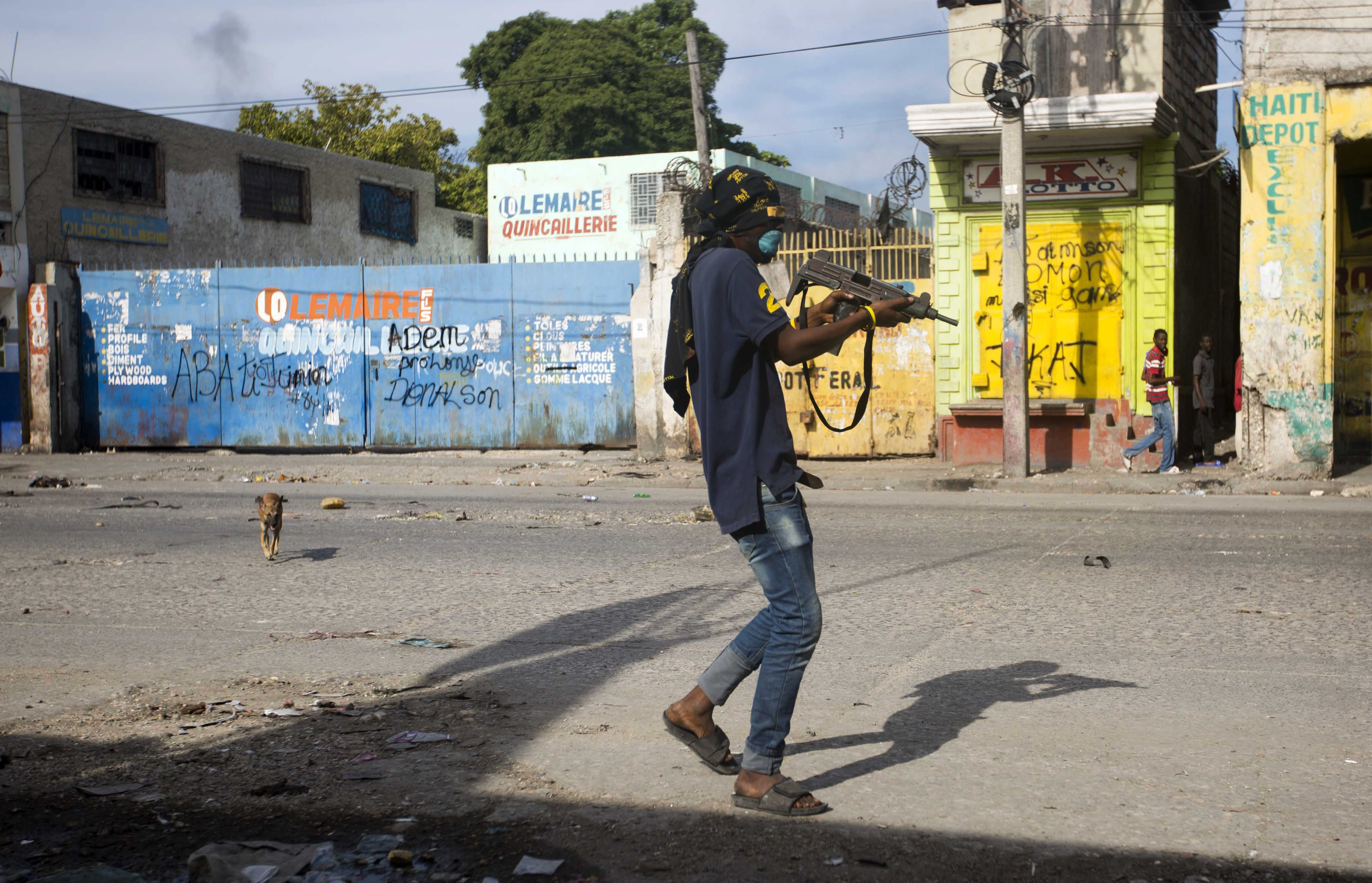 An armed civilian carries a weapon on during a shootout between rival gangs to take control of the Croix-des-Bossales market, on Boulevard Jean-Jacques Dessalines, a main commercial artery, in Port-au-Prince, Haiti, Wednesday, Nov. 21, 2018. The fight for control of the market, where vendors pay the controlling gang regular payments, erupted amid days of protests and a strike against alleged government corruption. (AP Photo/Dieu Nalio Chery)