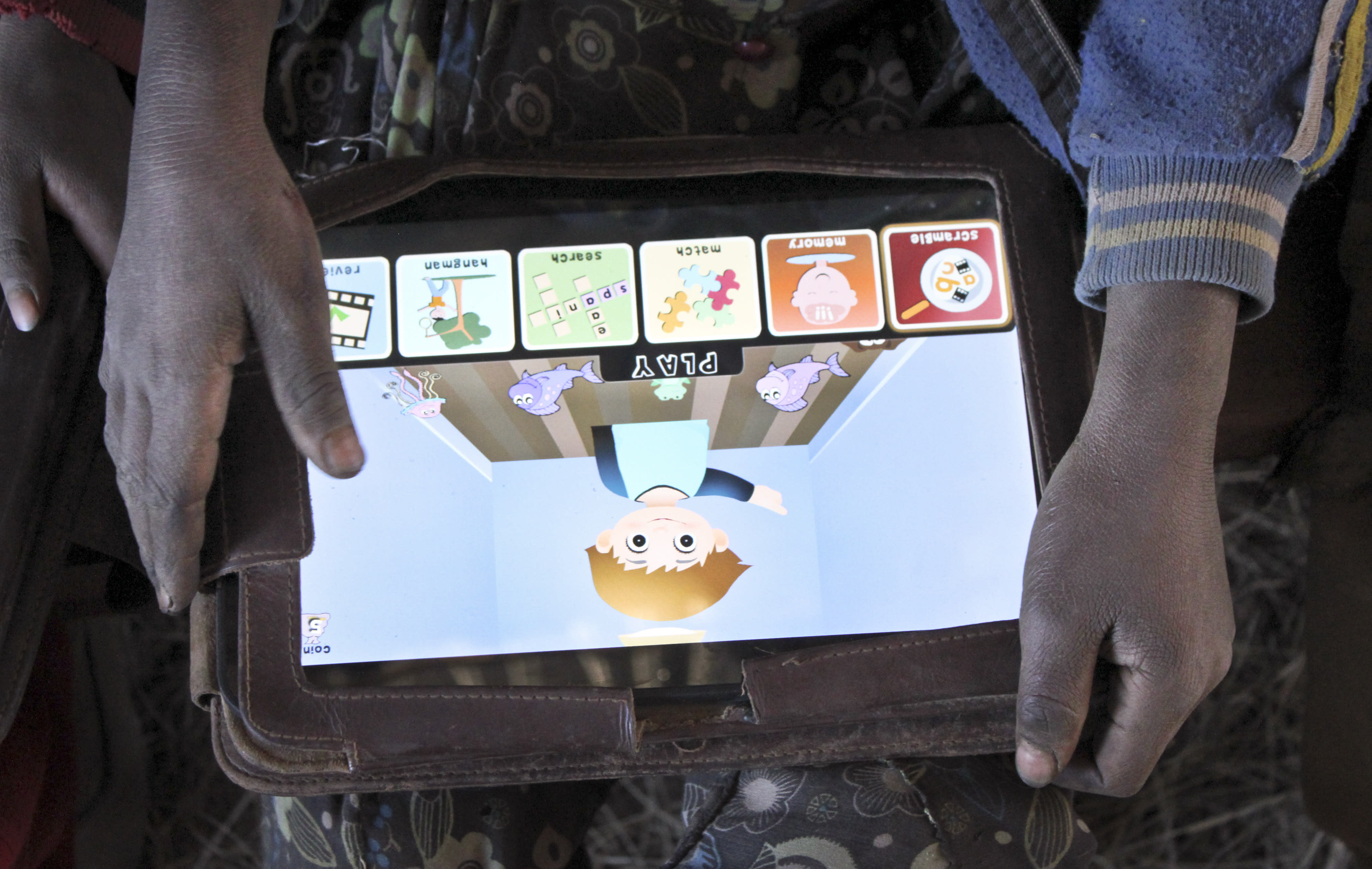 In this photo taken Tuesday, Nov. 27, 2012, a boy plays with a tablet computer given to the children by the One Laptop Per Child project in the village of Wenchi, Ethiopia. The project gave tablets to the children in the poor, illiterate village to see how much the children could teach themselves and now many kids can recite the English alphabet and spell words in English. (AP Photo/Jason Straziuso)
