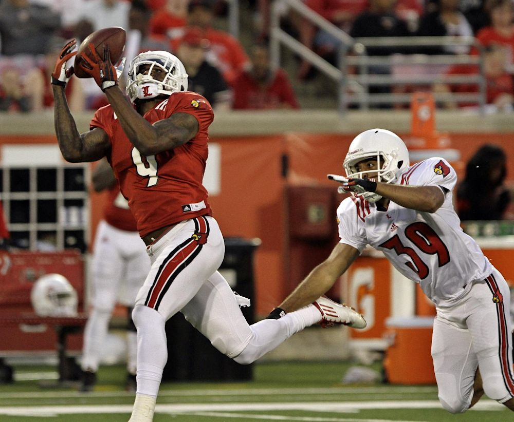 Louisville's senior wide receiver DeVante Parker (9) makes this catch after getting past defender Jordan Streeter (39) in their NCAA college spring football game in Louisville, Ky., Friday, April 11, 2014