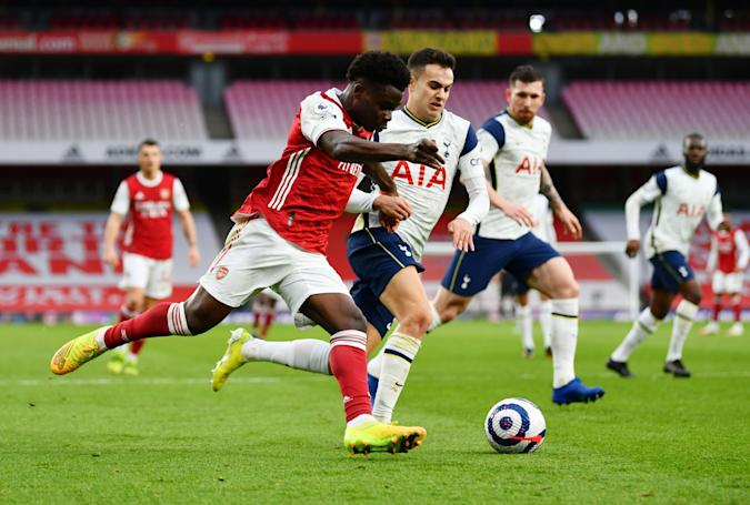 Soccer Football - Premier League - Arsenal v Tottenham Hotspur - Emirates Stadium, London, Britain - March 14, 2021 Arsenal's Bukayo Saka in action with Tottenham Hotspur's Sergio Reguilon Pool via REUTERS/Dan Mullan EDITORIAL USE ONLY. No use with unauthorized audio, video, data, fixture lists, club/league logos or 'live' services. Online in-match use limited to 75 images, no video emulation. No use in betting, games or single club /league/player publications.  Please contact your account representative for further details.