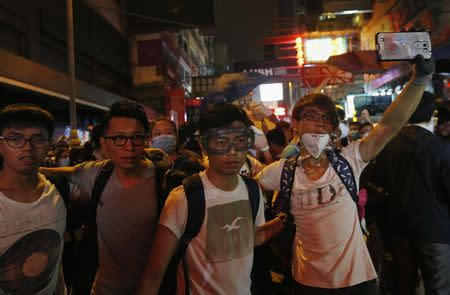 A pro-democracy protester takes a photo of the police near other protesters during a confrontation with the police at Mongkok shopping district in Hong Kong