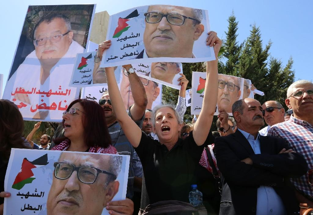 Protesters hold portraits of prominent Jordanian writer Nahed Hattar, who was shot dead the previous day outside an Amman court, during a demonstration in front of the prime minister's office on September 26, 2016 (AFP Photo/Khalil Mazraawi)
