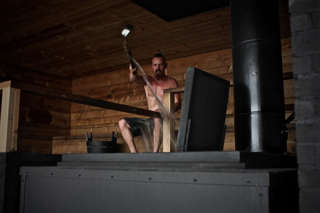 """Finnish actor Jasper Paakkonen throws water on the hot stones inside the new boutique sauna called Loyly (Finnish for """"Steam"""") in Helsinki on July 7, 2016 (AFP Photo/Sam Kingsley)"""