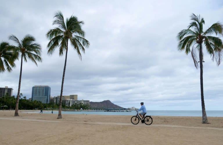 A cyclist rides along an empty Waikiki Beach in Honolulu, Hawaii as Hurricane Douglas veers northward, sparing Oahu from a direct hit (AFP Photo/Ronen ZILBERMAN)