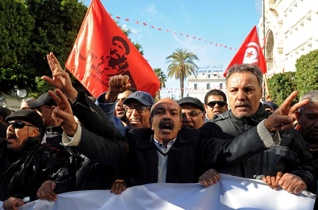 Protesters shout anti-government slogans outside the Tunisian General Labour Union headquarters on the seventh anniversary of the 2011 uprising (AFP Photo/Anis MILI)