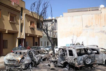 Damaged vehicles by an overnight shelling are seen in Abu Salim district in Tripoli,