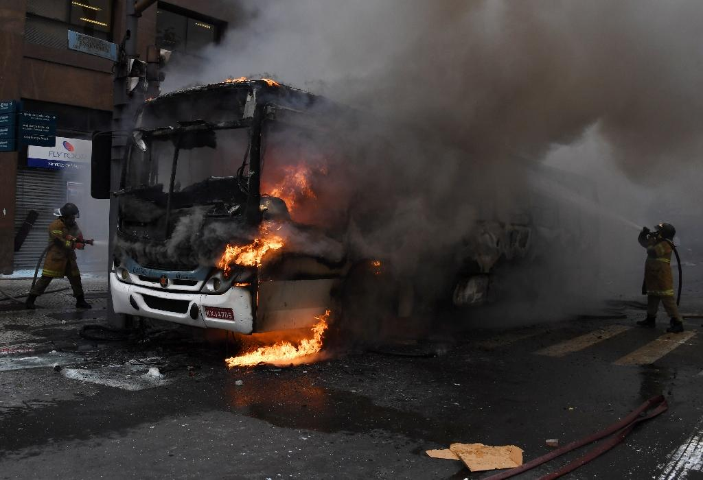 Civil servants protesting against austerity measures clash with riot police and set fire to a bus on Rio Branco, the main avenue in Rio de Janeiro, Brazil, while firefighters attempt to put out the blaze, on February 1, 2017 (AFP Photo/VANDERLEI ALMEIDA)