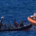 Migrants rescued after jumping overboard from ship being denied port in Italy