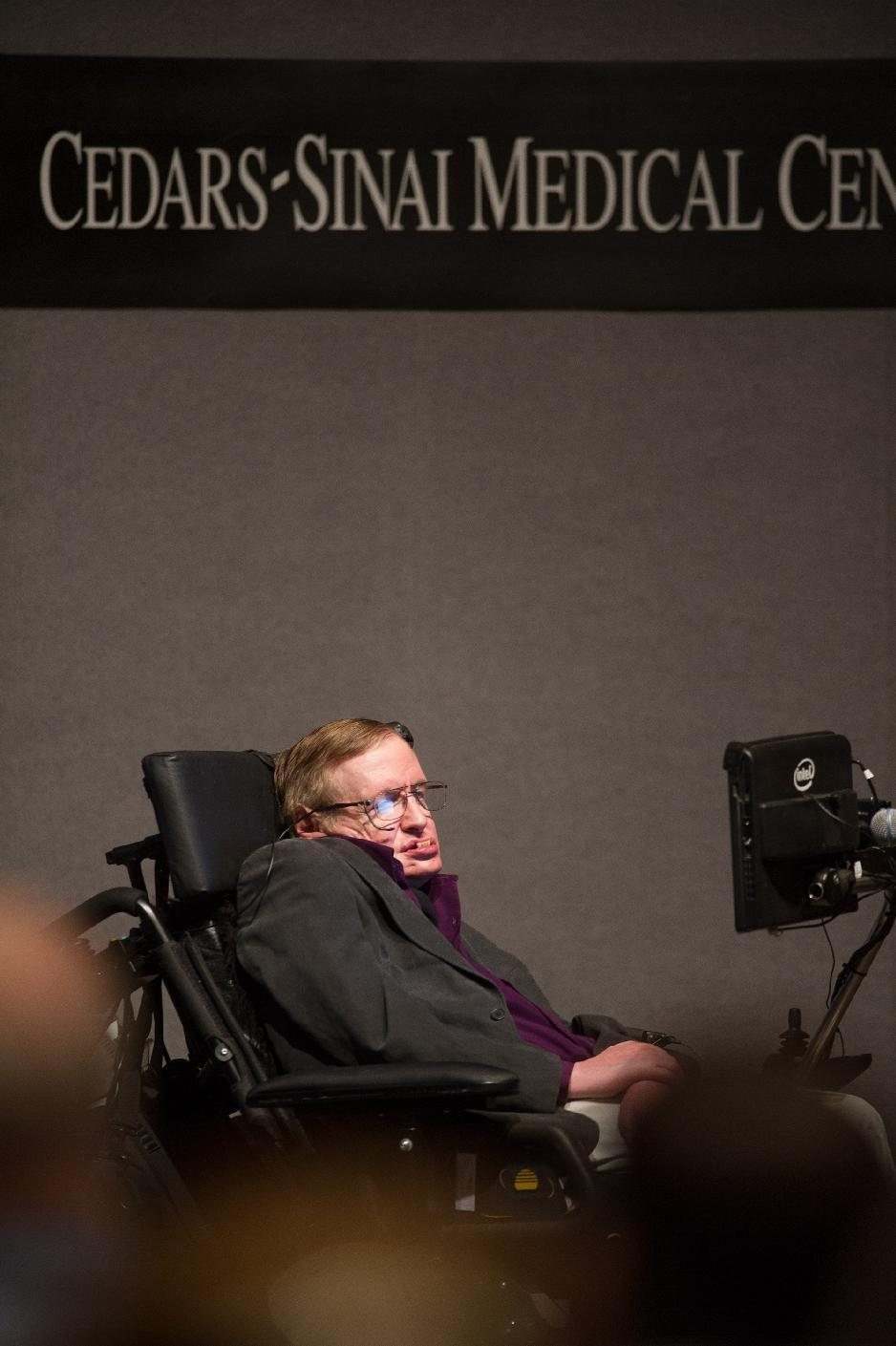 """In this photo provided by Cedars-Sinai, British cosmologist Stephen Hawking, who has motor neuron disease, gives a talk titled """"A Brief History of Mine,"""" to workers at Cedars-Sinai Medical Center in Los Angeles, on Tuesday, April 9, 2013. (AP Photo/Cedars-Sinai, Eric Reed)"""