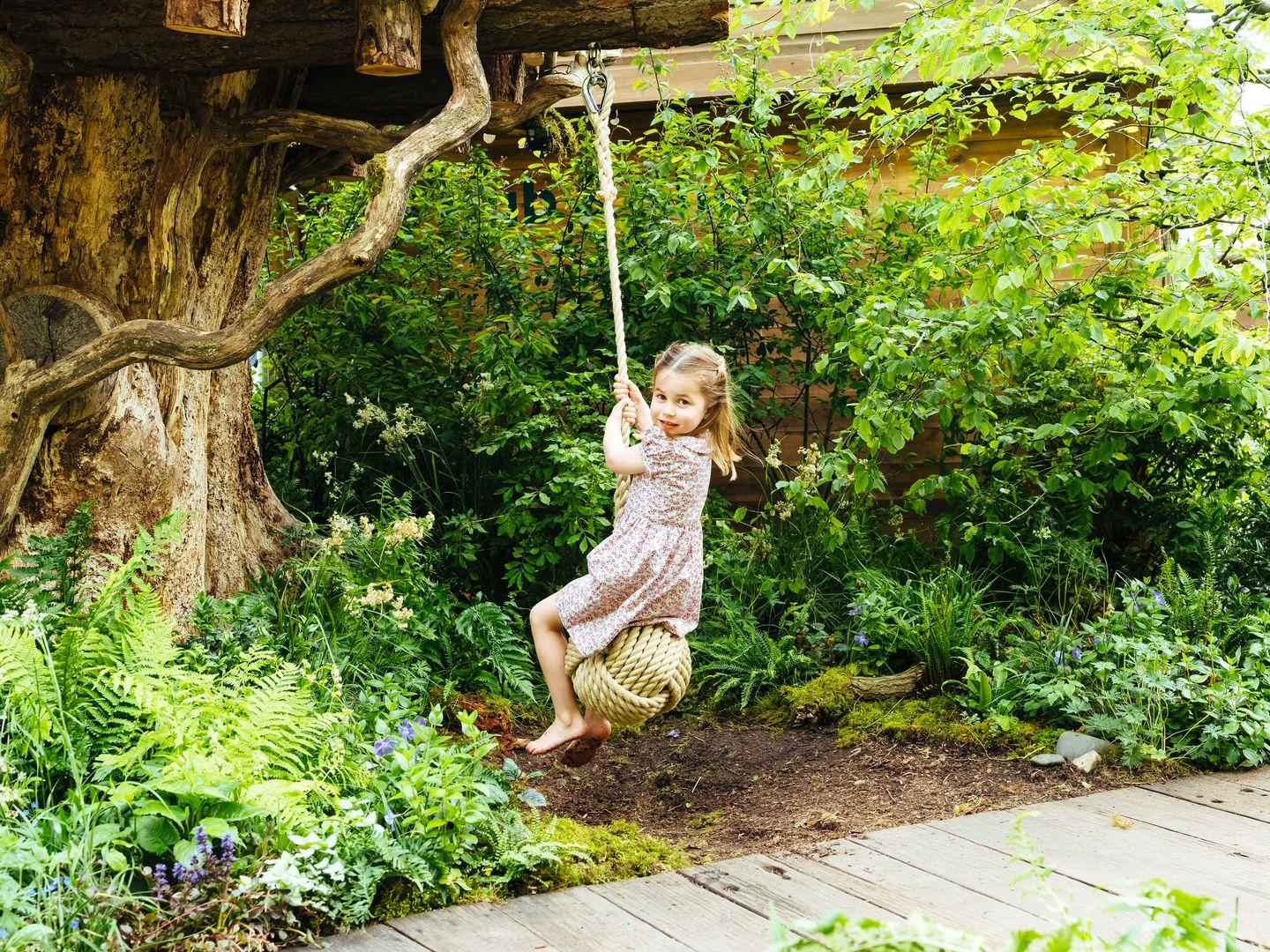 """<p>Princess Charlotte <a href=""""https://www.townandcountrymag.com/society/tradition/a27520757/kate-middleton-william-george-charlotte-louis-photos-chelsea-flower-show/"""" target=""""_blank"""">plays on a swing in the garden created</a> by her mom, the Duchess of Cambridge, at the Chelsea Flower Show. The royals released a number of sweet photos of George, Charlotte, and Louis playing in the new space, which was designed to encourage families to spend time in nature. </p>"""