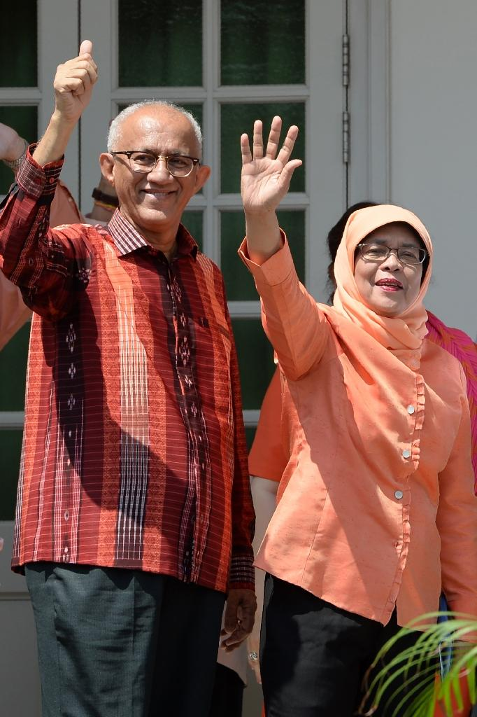 Former parliamentary speaker Halimah Yacob (R), who was named the country's new president, waves to supporters with her husband Mohammed Abdullah Alhabshee as they arrive at the nomination centre in Singapore on September 13, 2017 (AFP Photo/ROSLAN RAHMAN)