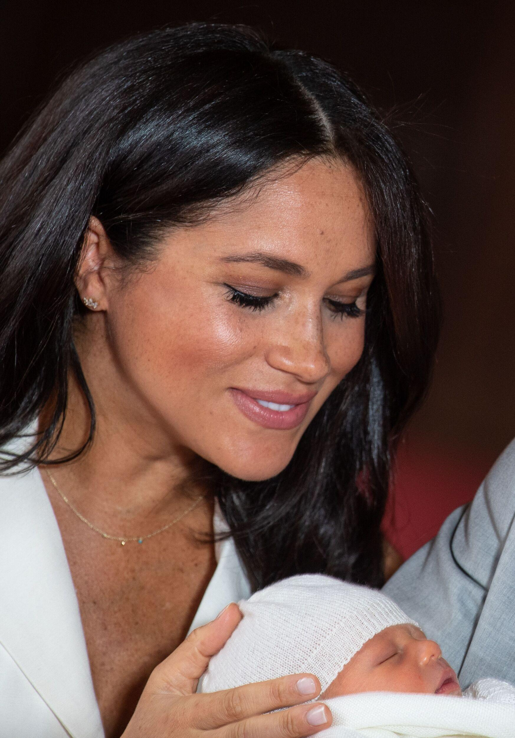 Meghan, Duchess of Sussex, places her hand on the head of her newborn baby boy as she and her husband Britain's Prince Harry, Duke of Sussex, pose for a photo in St George's Hall at Windsor Castle in Windsor, west of London on May 8, 2019. (Photo by Dominic Lipinski / POOL / AFP) (Photo credit should read DOMINIC LIPINSKI/AFP/Getty Images)