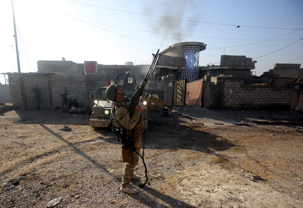 A member of the Iraqi forces fires a gun in Mosul's eastern Al-Intisar neighbourhood on December 30, 2016, during an ongoing military operation against Islamic State (IS) group jihadists (AFP Photo/AHMAD AL-RUBAYE)