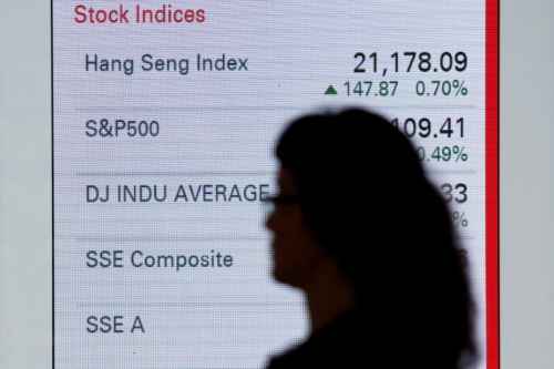 A woman walks past a panel displaying stock indices of various markets in Hong Kong