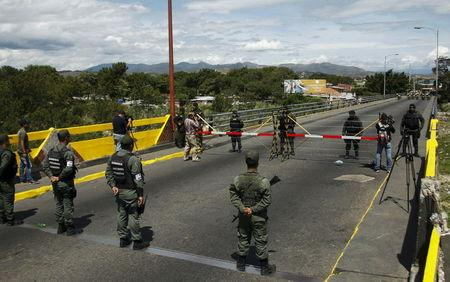Venezuela's National Guards stand in front of Colombia's soldiers at Simon Bolivar international bridge, on the border with Colombia, at San Antonio in Tachira state
