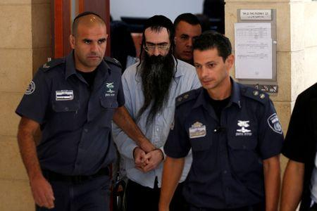 Yishai Schlissel (C), convicted of killing a woman during the 2015 Jerusalem Gay Pride Parade, is escorted by security personnel after he is sentenced at the Jerusalem District Court June 26, 2016. REUTERS/Ronen Zvulun