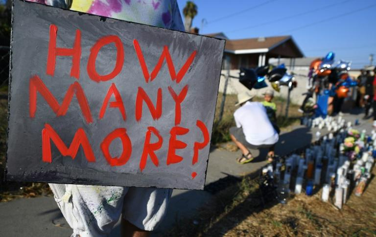 """A man holds a sign stating """"How Many More?"""" at a makeshift memorial on September 1, 2020 in Los Angeles, at the location where Dijon Kizzee was shot and killed the previous day by Los Angeles Sheriff's Deputies"""