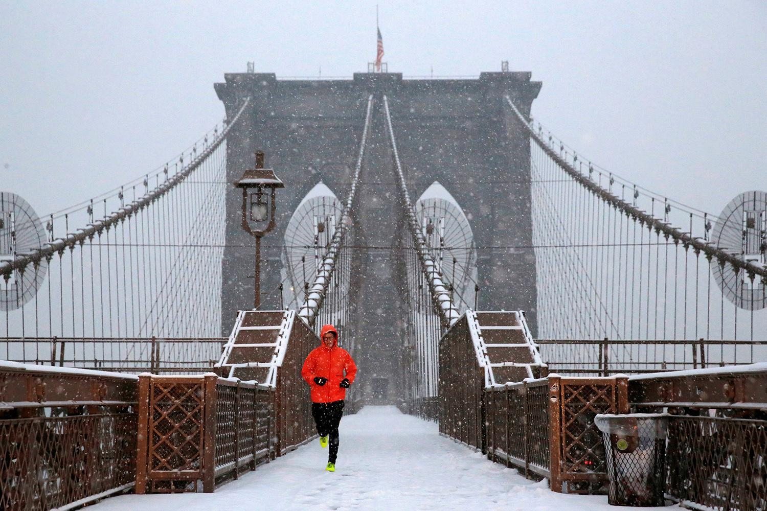 <p>A man runs over the Brooklyn Bridge during morning snow in Manhattan, New York City, Dec. 17, 2016. (Photo: Andrew Kelly/Reuters) </p>