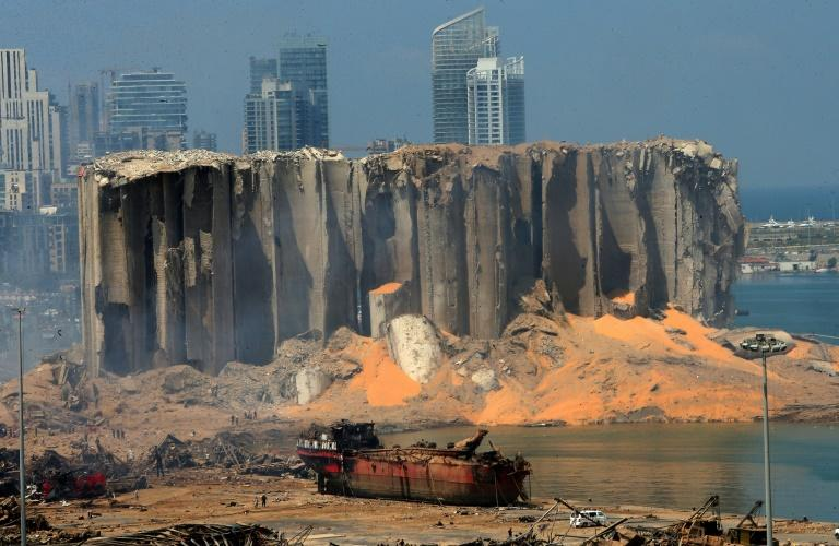 A picture taken on August 5, 2020 shows the damaged grain silo and a burnt boat at Beirut's harbour, a day after a powerful explosion tore through Lebanon's capital,when a huge depot of ammonium nitrate ignited at the city's main port (AFP Photo/STR)