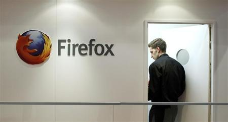A man is seen next to a Firefox logo at a Mozilla stand during the Mobile World Congress in Barcelona