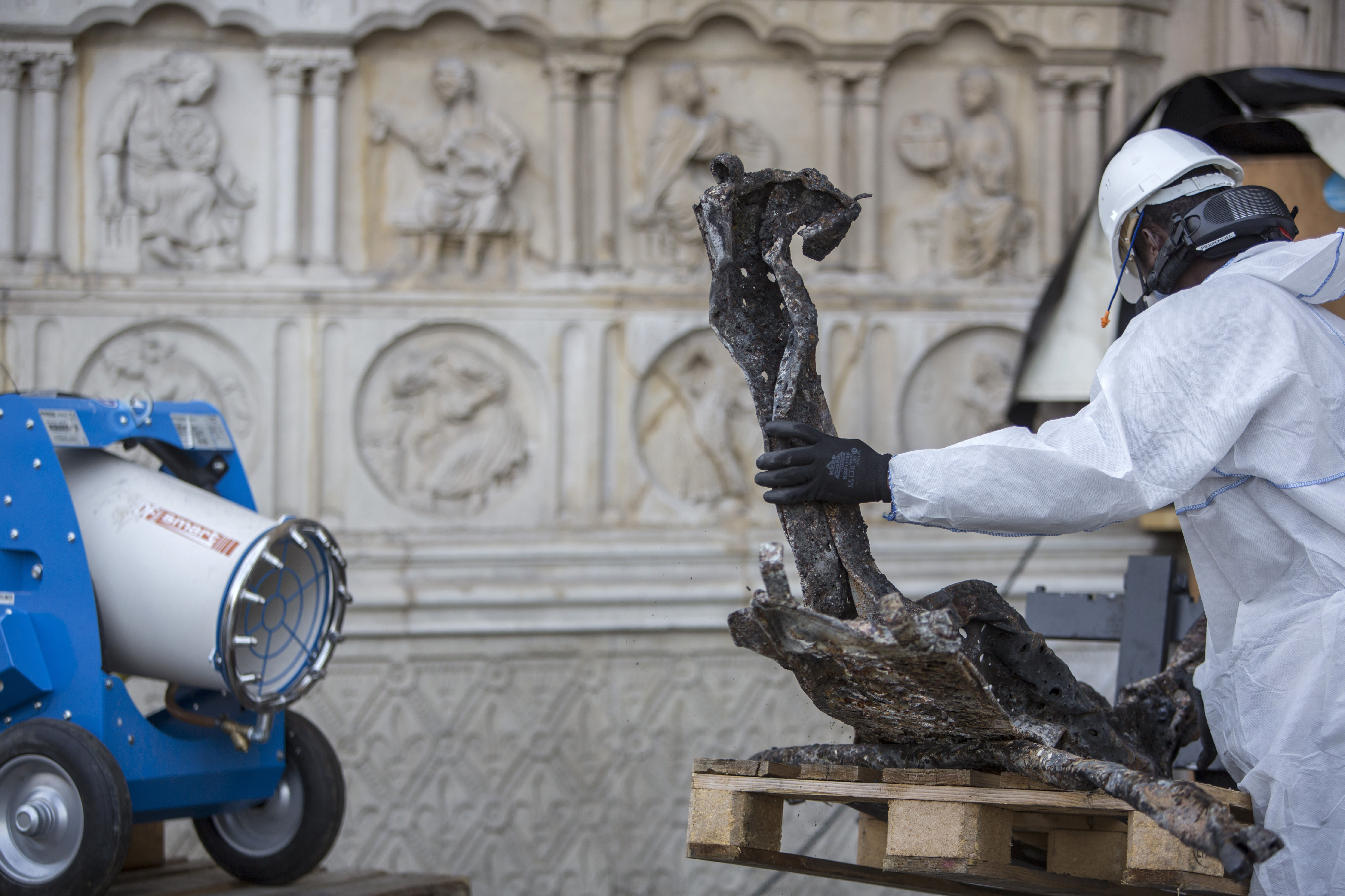 A worker cleans debris, during preliminary work to repair the fire damage at the Notre-Dame de Paris Cathedral, in Paris, France, Wednesday, July 24, 2019. (AP Photo/Rafael Yaghobzadeh, Pool)