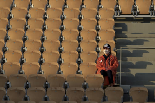 A stadium employee sits amidst rows of empty seats at center court Philippe Chatrier during the first round match of the French Open tennis tournament between Spain's Rafael Nadal and Egor Gerasimov of Belarus at the Roland Garros stadium in Paris, France, Monday, Sept. 28, 2020. (AP Photo/Michel Euler)