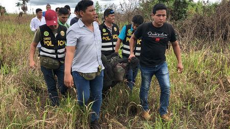 Police officers carry the body of Sebastian Woodroffe, a 41-year-old Canadian citizen, who was beaten and strangled with a rope in the jungle region of Ucayali on Friday after members of an indigenous community accused him of killing a revered medicine woman, in Pucallpa, Peru April 21, 2018. REUTERS/ Hugo Enrique Alejos