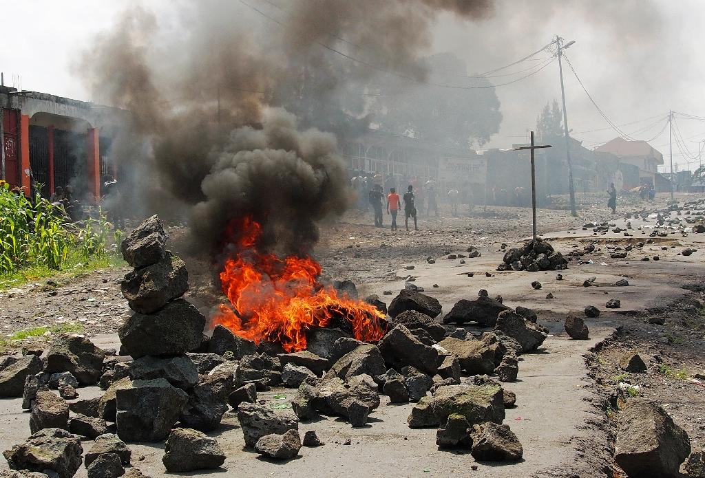 People walk past a burning barricade during a protest against President Joseph Kabila, in Goma on May 26, 2016 (AFP Photo/Fiston Mahamba)